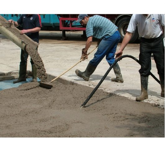 Worker using the Belle vibratech high frequency poker in wet concrete onsite