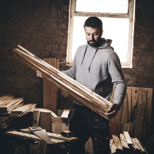 Man wearing the grey Scruffs worker hoodie and Scruffs work trousers whilst holding planks of wood