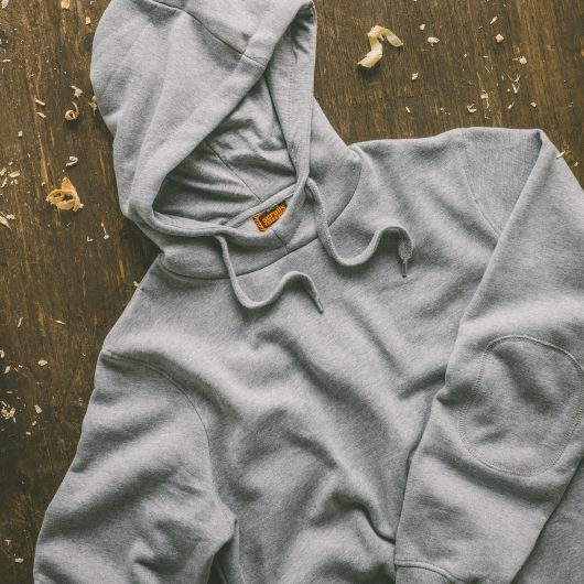 Grey Scruffs worker hoodie laid on wooden surface with sawdust around it