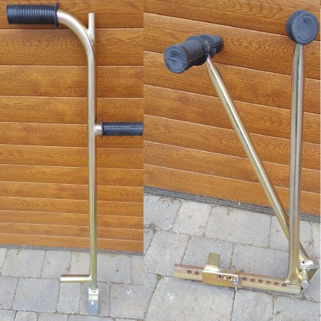 Galvanised metal block paving gap wedge and block lifter with black rubber handles leaning against a wall