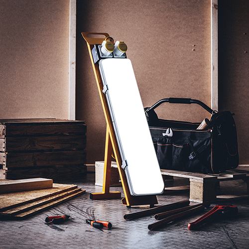 Defender 2ft LED contractor light turned on next to tool box, tools scattered on floor and wooden planks and box