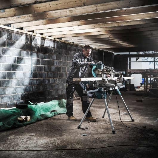 Worker wearing the Scruffs pro softshell jacket in charcoal whilst using a circular saw onsite