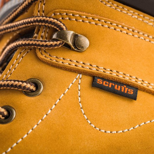 Close up of black label with orange Scruffs text logo on the side of the Sharpe boot