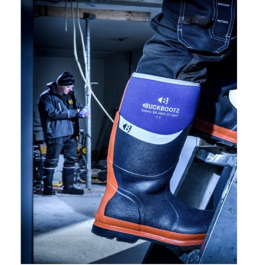 Worker wearing blue Buckler BBZ6000 safety wellies climbing a ladder whilst another worker is wearing black version in background