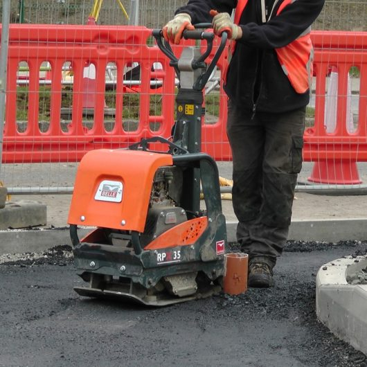 Worker in safety clothing and boots using the Belle RPX 35 reversible plate compactor on fresh tarmac