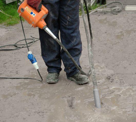 Worker using the Belle megavib+ vibrating concrete poker in wet concrete