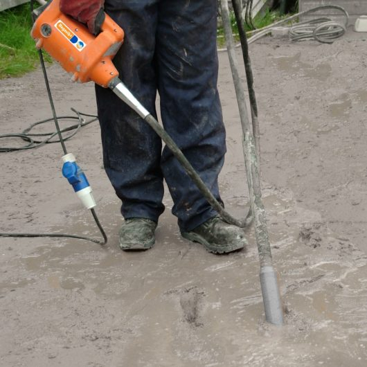 Worker using the Belle megavib+ vibrating concrete poker in wet concrete