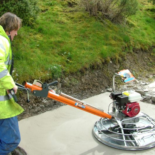 Worker wearing protective clothing whilst using the Belle pro tilt trowel on some concrete