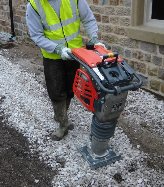 Worker wearing safety clothing using the Belle RTX 60 trench rammer on gravel