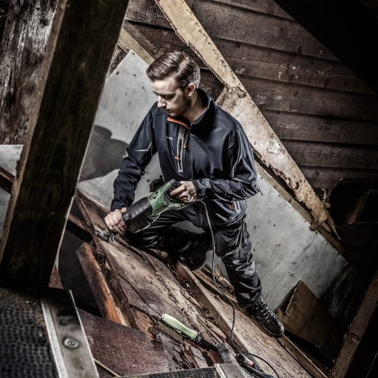 Worker wearing the Scruffs pro softshell jacket in black whilst using a nail gun