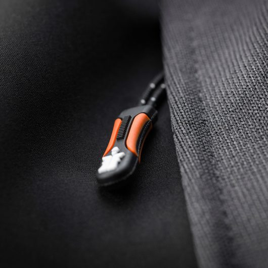 Close up of the black zip with orange detailing and white Scruffs logo on the graphite trade tech softshell jacket