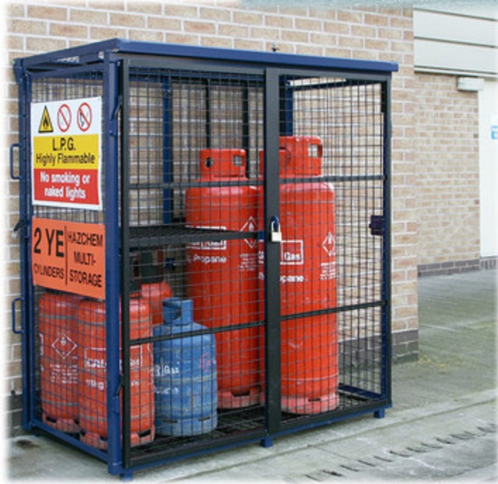 Multiple different size gas bottles in blue DQGC60 fold away gas cage with safety signs on and padlocked doors