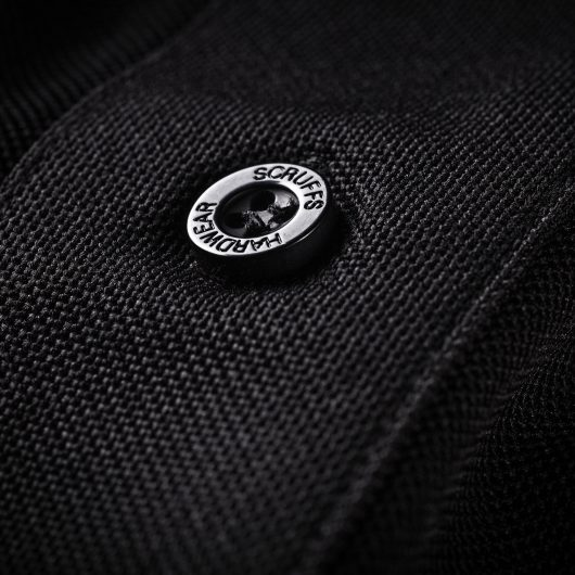 Close up of a Scruffs branded button on the chest button placket of the black trade active polo