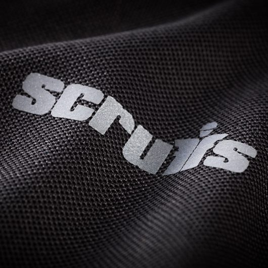 Close up of the Scruffs logo in contrasting grey text on the chest of the black trade active polo