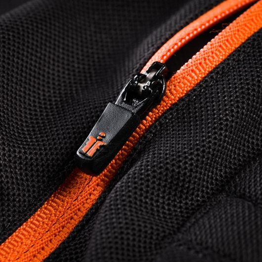 Close up of the black and orange zip on the chest of the Scruffs trade active polo with orange Scruffs logo at bottom of zip