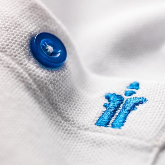 Close up of the chest pocket on the white worker polo with blue button in centre of pocket and blue scruffs logo to the right