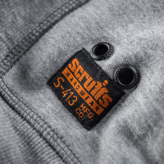 Close up of Scruffs logo with black background and orange text on the bottom left back of the Scruffs trade sweatshirt